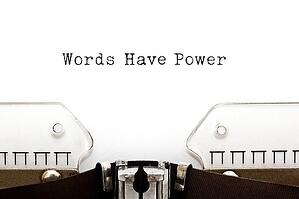 A page in a typewriter features the copy Words Have Power.