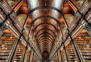 A vast library filled with sleek angles and rows and rows of books.
